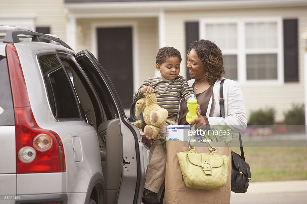 Mother unloading son and groceries from van
