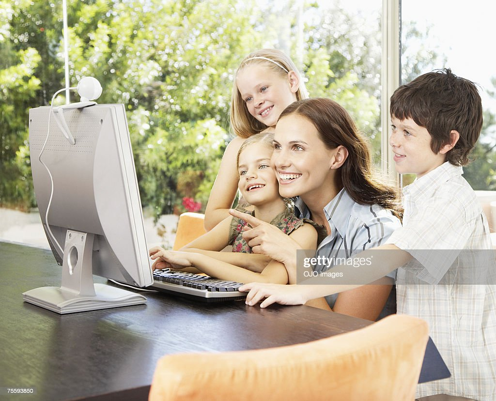 A mother using a computer with her three young kids : Stock Photo
