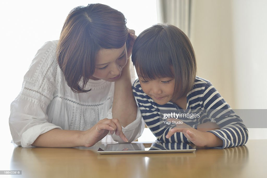 Mother using a digital tablet with daughter : Stock Photo