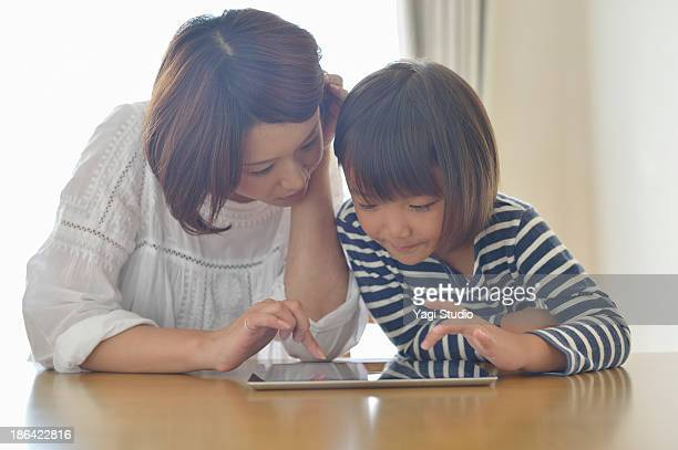 Mother using a digital tablet with daughter