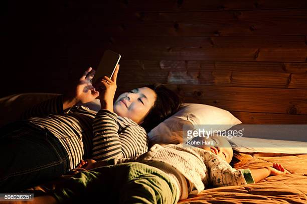 Mother using a smart phone on the bed at night