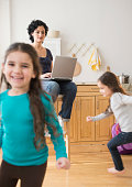 Mother using laptop as daughters play