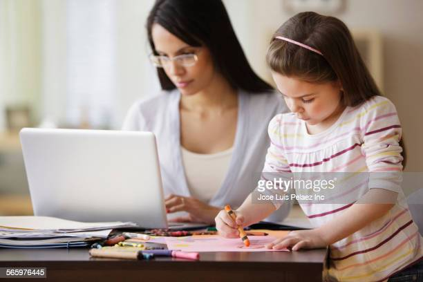 Mother using laptop near daughter drawing at desk