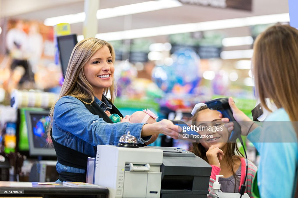 Mother using smart phone to pay for purchases in store : Stock Photo