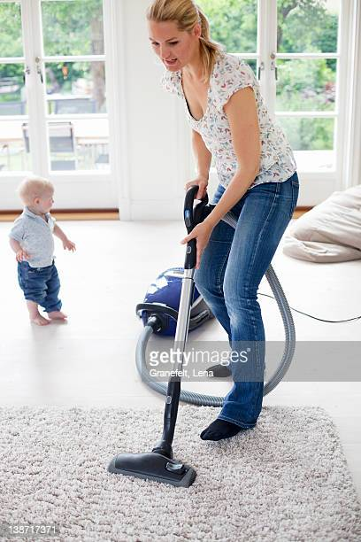 Mother vaccuming the livingroom