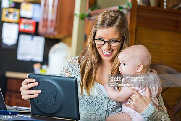 Mother video chatting with baby daughter on digital tablet device