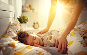 mother wakes up sleeping child daughter girl in the morning