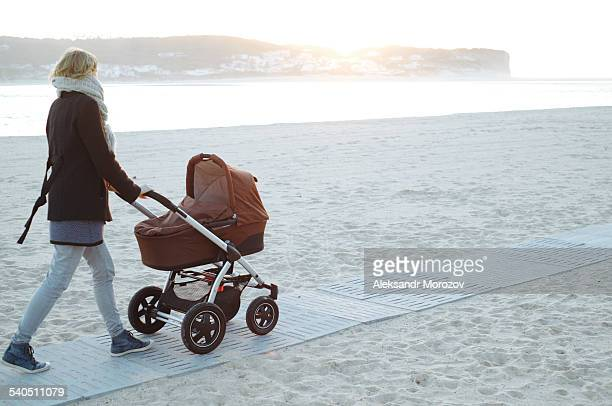 Mother walking on beach with baby stroller