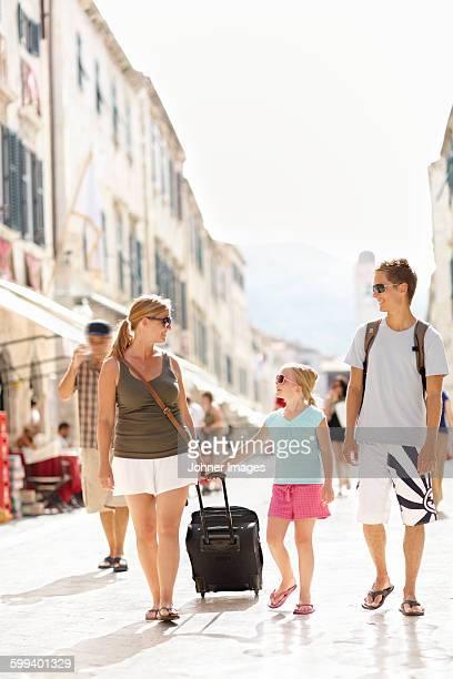 Mother walking with children through city street