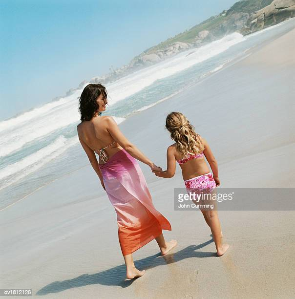 Mother Walking With Her Child Hand in Hand Along a Beach