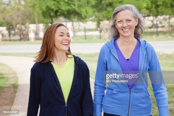 Mother Walking With Her Daughter While Exercising at Park