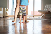 Mother walking with little boy at home on wood floor