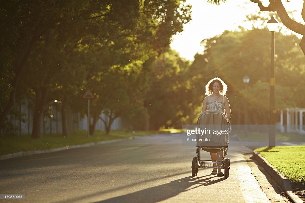 Mother walking with stroller at sunset