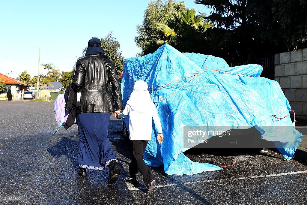 A mother walks her child to school past a fire-bombed vehicle outside the Australian Islamic College and Mosque on June 29, 2016 in Perth, Australia. Police are investigating a firebomb attack which occurred last night at the Thornlie Mosque. No one was injured in the attack which took place during evening prayers.