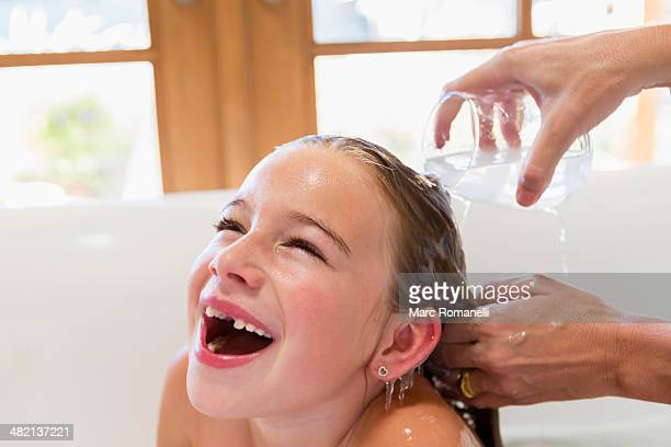 Mother washing daughter's hair