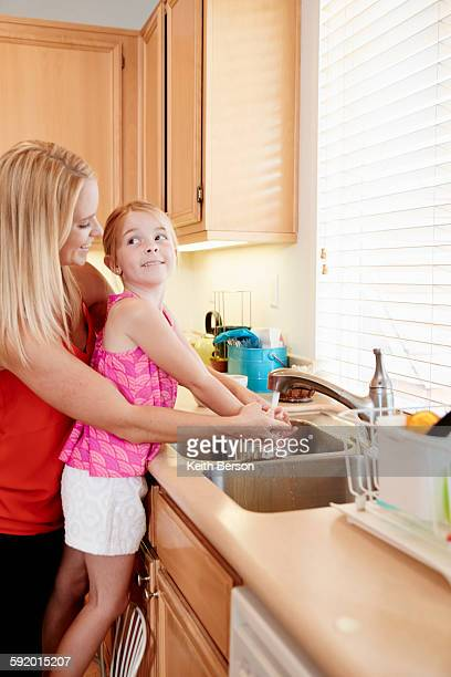 Mother washing daughters hands in kitchen sink