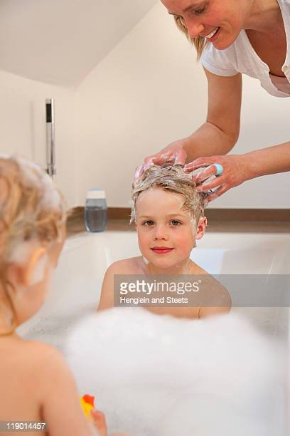 Mother washing sons hair in bathtub