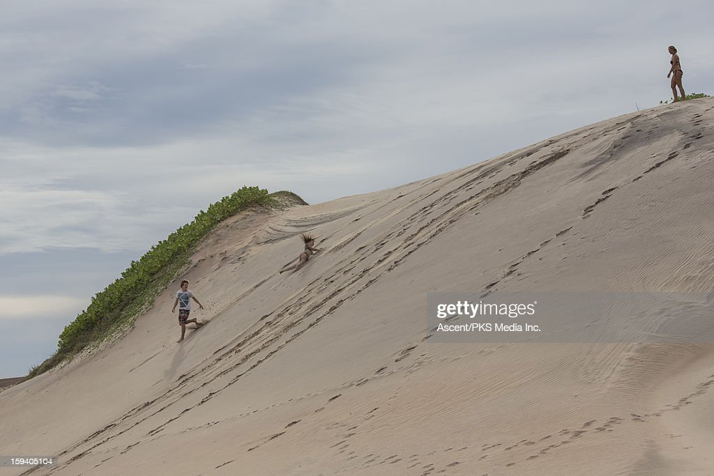 Mother watches as kids roll and run down sand hill : Stock Photo