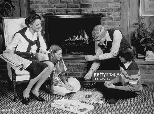 A mother watches her family playing a board game