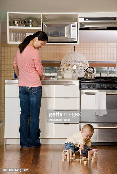 Mother watching baby boy (15-18 months) playing with building blocks