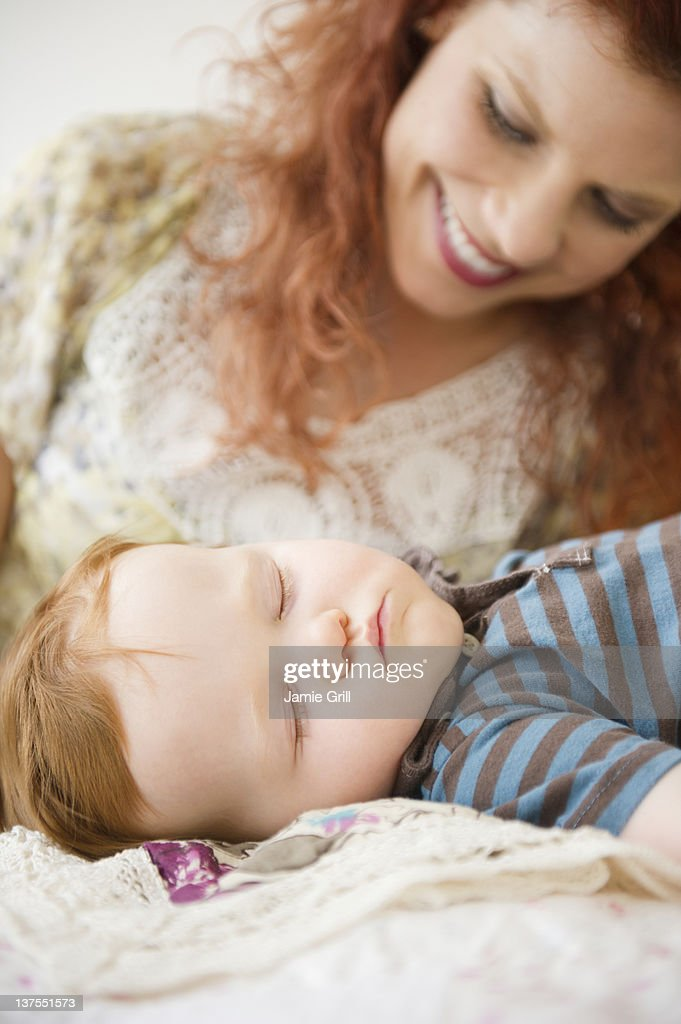 Adult Child And Parent Sleeping In Same Bed