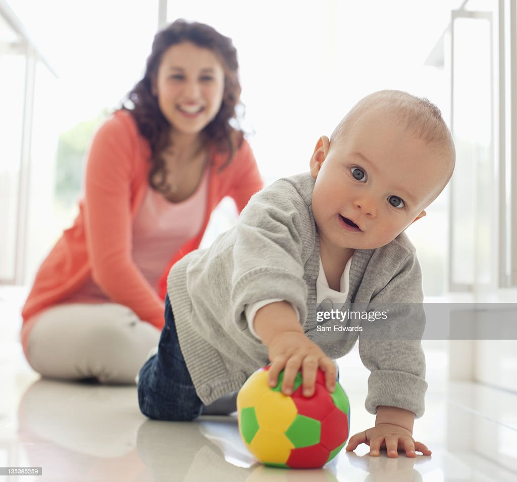 Mother watching baby playing with ball