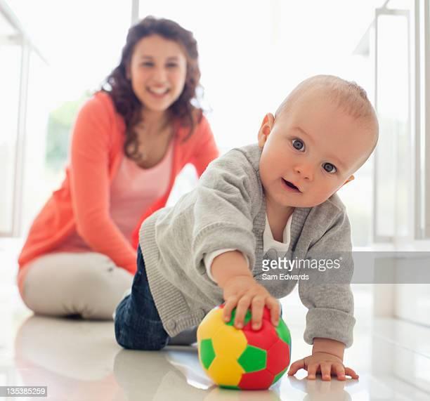 Madre viendo niños jugando con bola