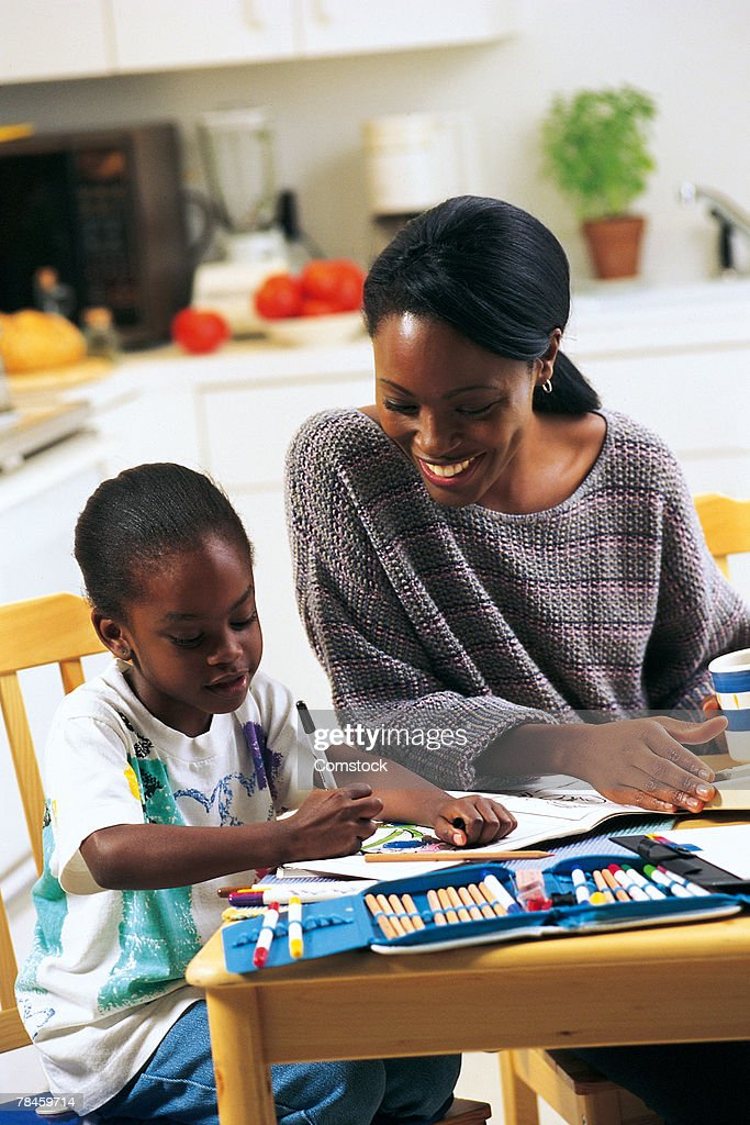 Mother watching daughter color in kitchen : Stock Photo