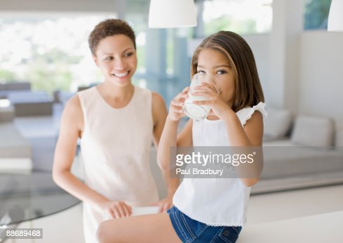 Mother watching daughter drink glass of milk : Stock Photo