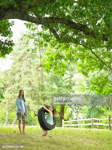 Mother watching daughter (4-5) playing on tire swing