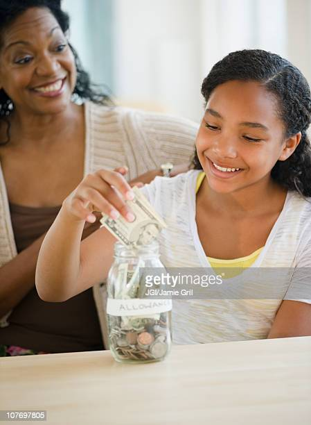 Mother watching daughter put money into jar