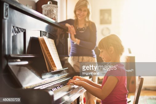 Mother watching daughter that is playing piano