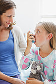 Mother watching daughter using asthma inhaler