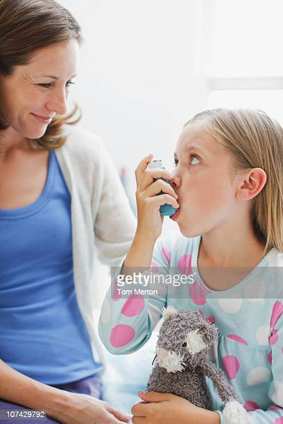 Mother watching daughter using asthma inhaler