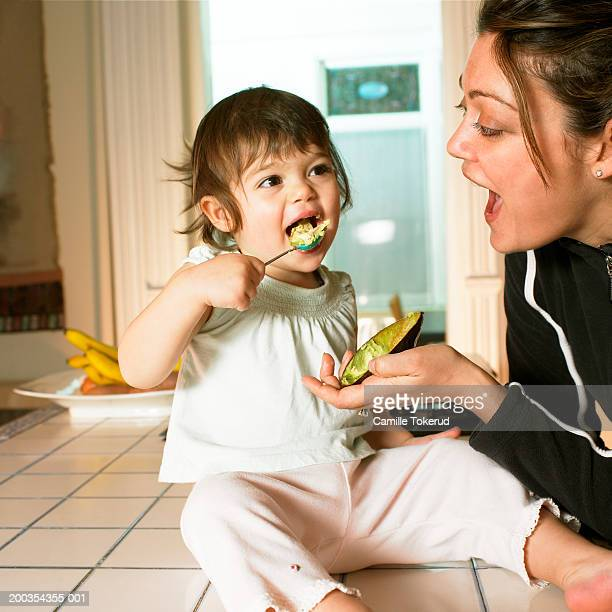 Mother watching female toddler (18-21 months) eating avocado