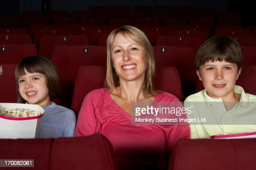Mother Watching Film In Cinema With Two Children : Stock Photo