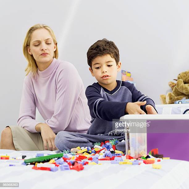 mother watching her son playing with toys on the bed