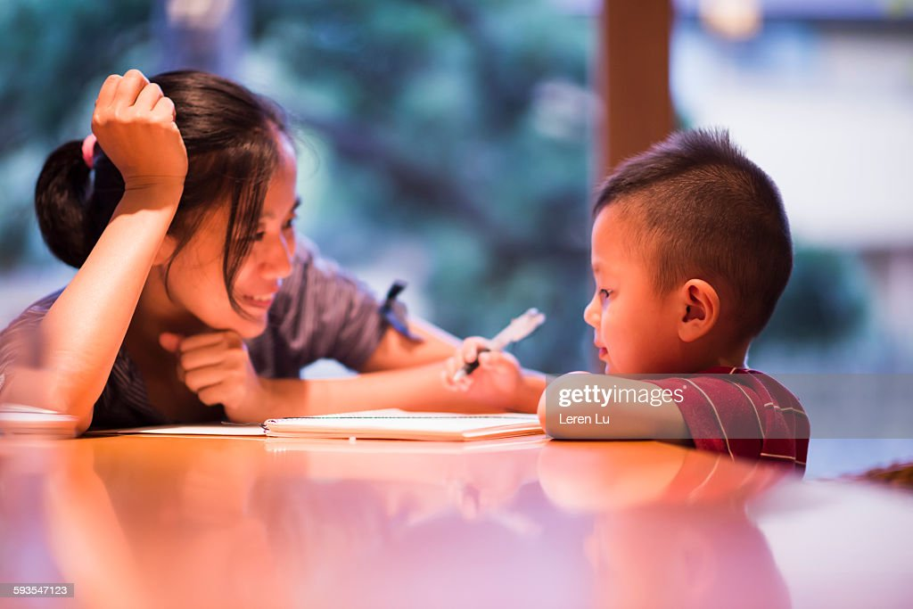 Mother watching kid drawing on paper