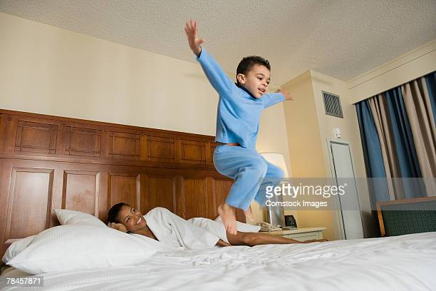 Mother watching son jump on bed