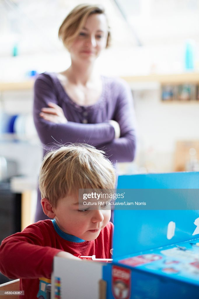 Mother watching son open new toy : Stock Photo