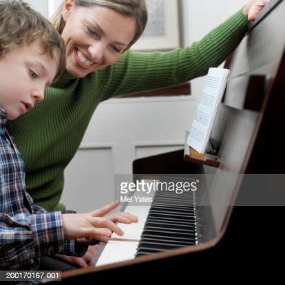 Mother watching son (4-6) playing piano, close-up