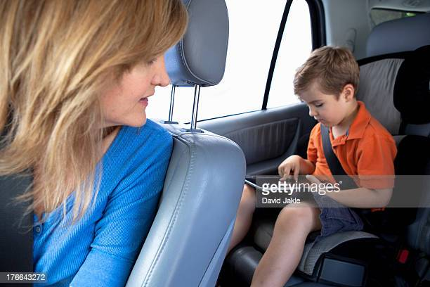 Mother watching son use digital tablet in back seat of car
