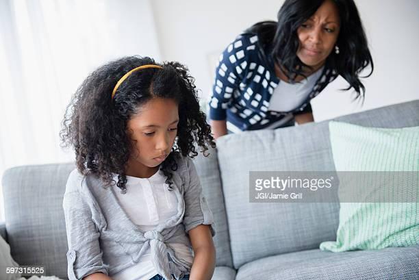 Mother watching sulking daughter