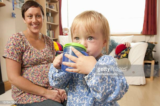 Mother watching toddler drink from cup