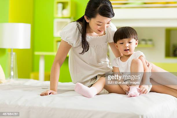 Mother watching young daughter putting her socks on