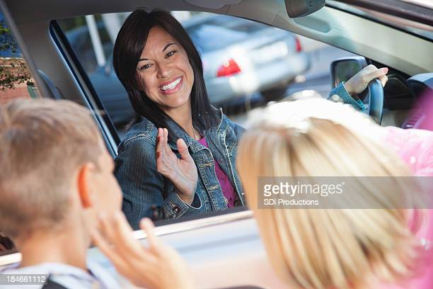 Mother waving bye to her children after school dropoff.