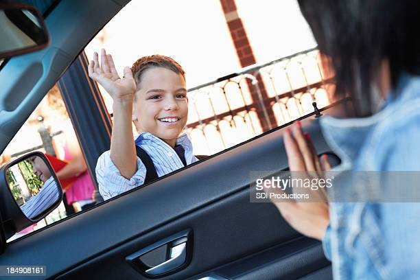 Mother waving to son as he's dropped off at school