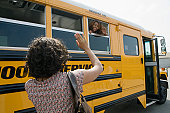 Mother Waving to Teenage Daughter on School Bus