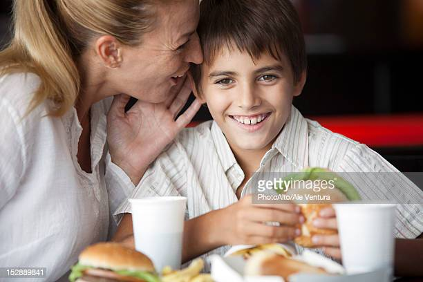 Mother whispering in son's ear in fast food restaurant
