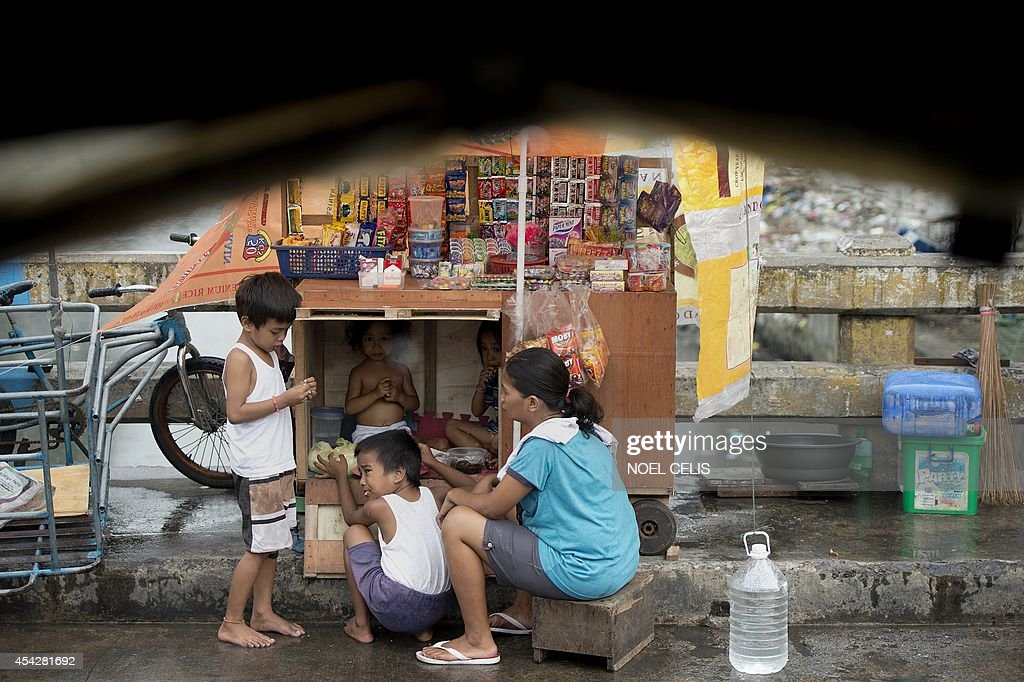 A mother who sells various items like cigarettes and candies on a wooden cart eats lunch with her children along a street in Manila on August 28, 2014. The Philippine economy rebounded to post 6.4-percent growth in the second quarter and regain its status as one of the strongest in Asia, authorities said on August 28. Officials said in April that amongst their new targets is the lowering of the country's poverty incidence from 25.2 percent of the population in 2012 to 18.0 to 20.0 percent by 2016.